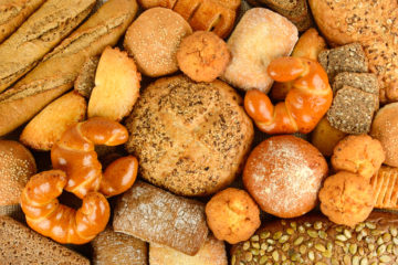 Collection of bread products (buns, baguettes, cereal bread, muffins, ciabatta, croissants) Top view.