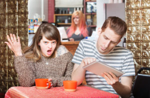 Insulted woman at table with young man using tablet