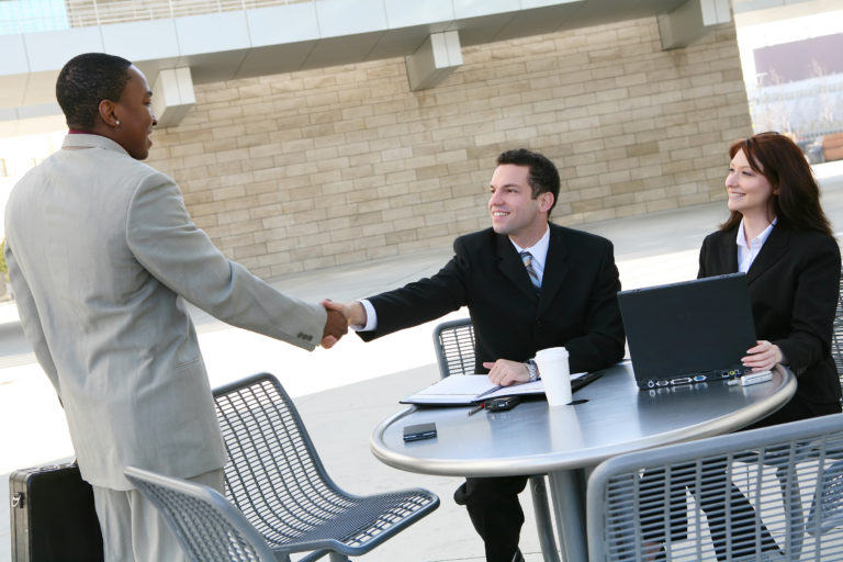 An attractive diverse business man and woman team shaking hands at office building