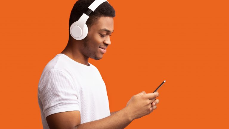 Enjoy Music. Smiling Man Listening To Podcast On Cellphone