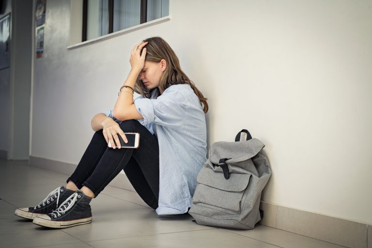 upset girl sitting in hallway