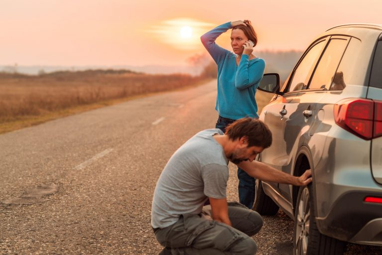 couple on side of road with flat tire